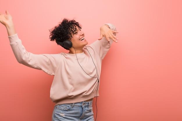 Junge afroamerikanerfrau mit einem muttermal, das musik mit einem kopfhörer tanzt und hört Premium Fotos