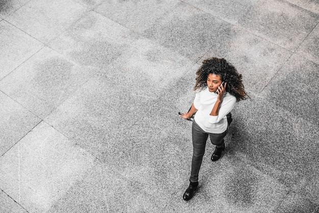 Junge afroamerikanergeschäftsfrau, die am telefon auf ihrem weg zum arbeitsplatz spricht. Premium Fotos