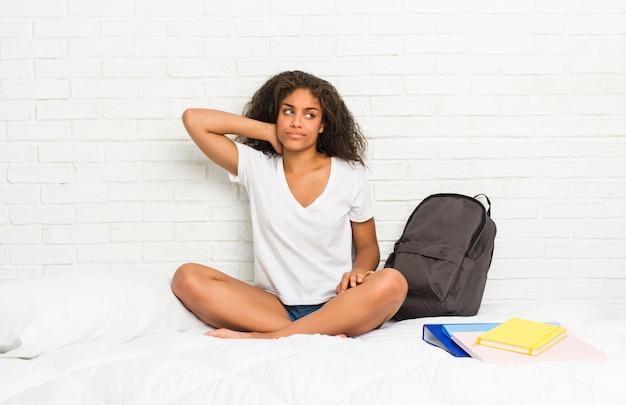 Junge afroamerikanerstudentenfrau auf dem bett, das zurück vom kopf berührt, eine wahl denkt und trifft. Premium Fotos