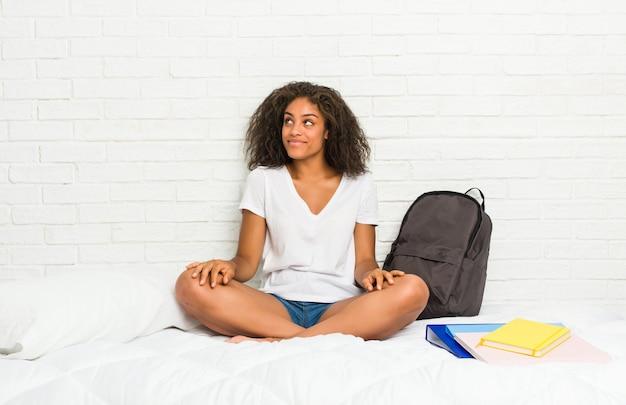 Junge afroamerikanerstudentenfrau auf dem bett träumend vom erreichen von zielen und von zwecken Premium Fotos