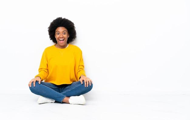 Junge afroamerikanische frau, die auf dem boden mit überraschendem gesichtsausdruck sitzt Premium Fotos