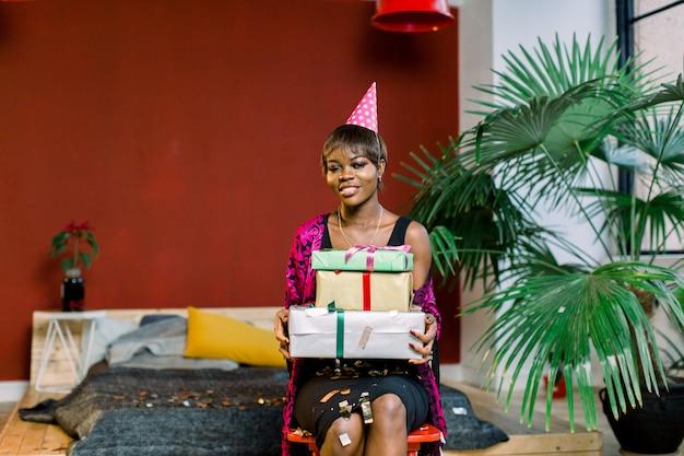 Junge afroamerikanische frau in einem geburtstagshut, der geschenkboxen hält Premium Fotos
