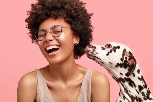 Junge afroamerikanische frau mit glitzer auf gesicht und ihrem hund Kostenlose Fotos