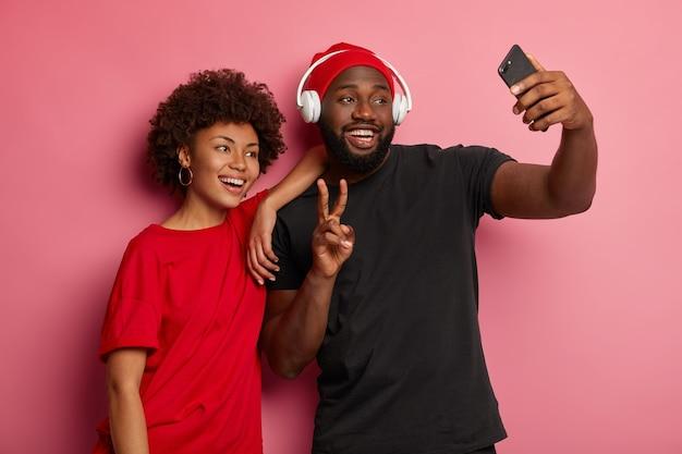 Junge afroamerikanische frauen und männer machen selfies auf modernen geräten, machen friedensgesten und lächeln glücklich in die kamera Kostenlose Fotos