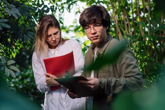 Junge agraringenieure, die im gewächshaus arbeiten Kostenlose Fotos