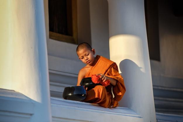 Junge anfängermönche sitzen reinigungsalmosenschüssel im kloster der große fenstertempel Premium Fotos