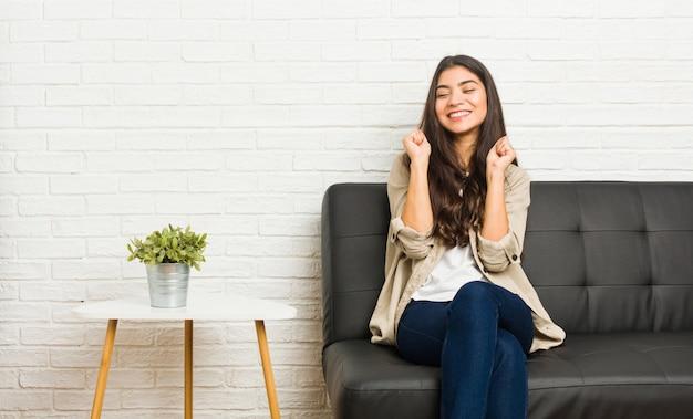 Junge arabische frau, die auf dem sofa anhebt faust sitzt, glücklich und erfolgreich sich fühlt. sieg-konzept. Premium Fotos
