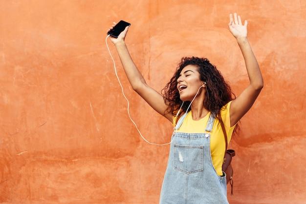 Junge arabische frau, die draußen musik mit kopfhörern hört Premium Fotos