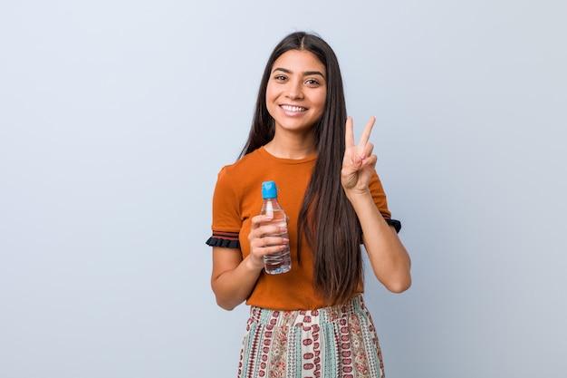 Junge arabische frau, die eine wasserflasche zeigt siegeszeichen und breit lächelt hält. Premium Fotos