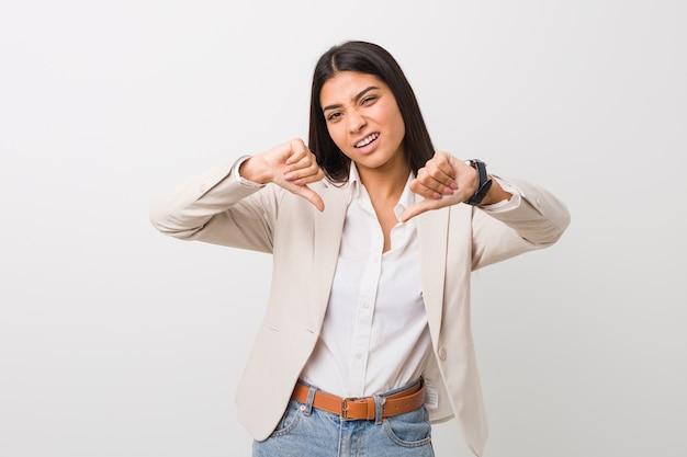 Junge arabische geschäftsfrau, die unten daumen zeigt und abneigung ausdrückt. Premium Fotos
