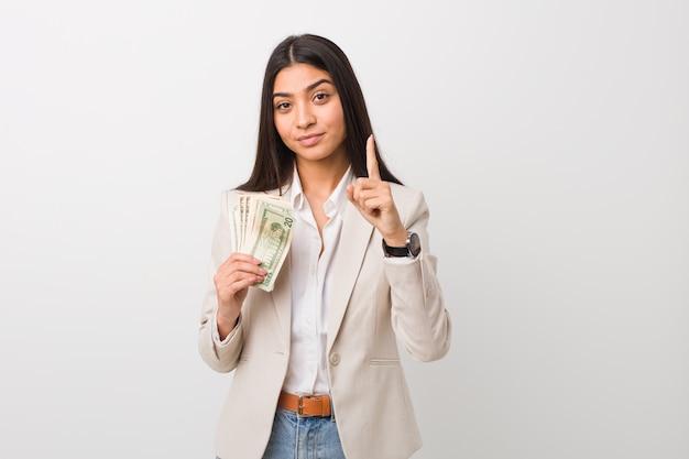 Junge arabische geschäftsfrau, welche die dollar zeigen nummer eins mit dem finger hält. Premium Fotos