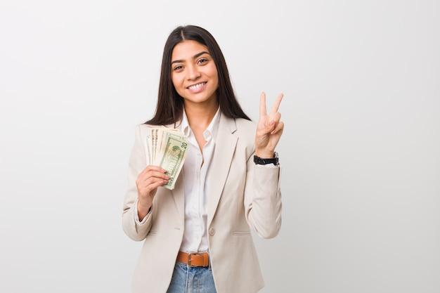 Junge arabische geschäftsfrau, welche die dollar zeigen nummer zwei mit den fingern hält. Premium Fotos