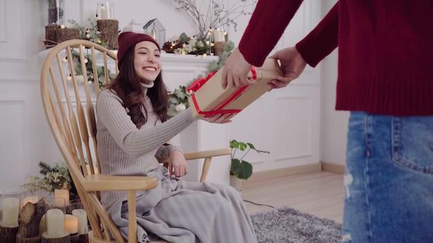 Junge asiatin, die auf einem stuhl zu hause eingewickelt in der grauen decke in ihrem wohnzimmer sitzt. Kostenlose Fotos