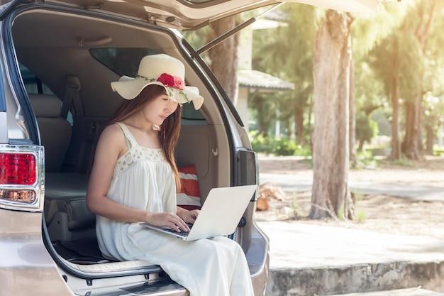 Junge asiatin, die laptop im kleid sitzt im auto, mädchenfreiberuflerfunktion verwendet Premium Fotos