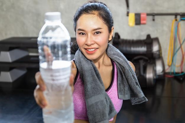 Junge asiatin in trinkwasser der sportkleidung nach training an der eignungsturnhalle. Premium Fotos