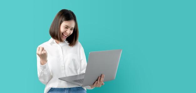 Junge asiatin lächelnd, laptop-computer mit der fausthand halten und für erfolg aufgeregt. Premium Fotos