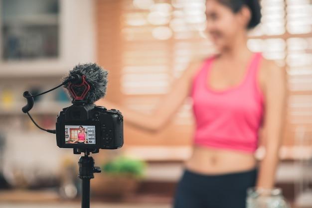 Junge asiatische bloggerfrauenübung und schauen zur kamera in der küche Kostenlose Fotos