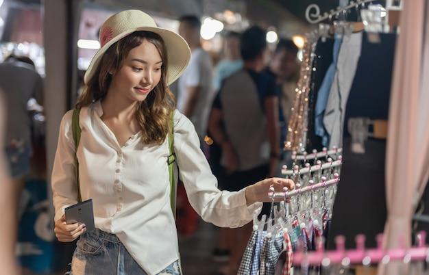 Junge asiatische einkaufsfrau, die stoffe am nachtmarkt wählt und kauft Premium Fotos