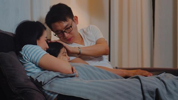 Junge asiatische familie las märchen zur tochter zu hause. glückliche japanische mutter, vater entspannen sich mit kleinem mädchen genießen die gute qualitätszeit, die auf bett liegt, bevor sie im schlafzimmer am haus nachts schlafen geht. Kostenlose Fotos