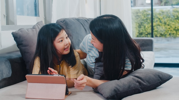 Junge asiatische familie und tochter glücklich, tablette zu hause verwendend. japanische mutter entspannen sich mit dem aufpassenden film des kleinen mädchens, der auf sofa im wohnzimmer am haus liegt. lustige mutter und schönes kind haben spaß. Kostenlose Fotos