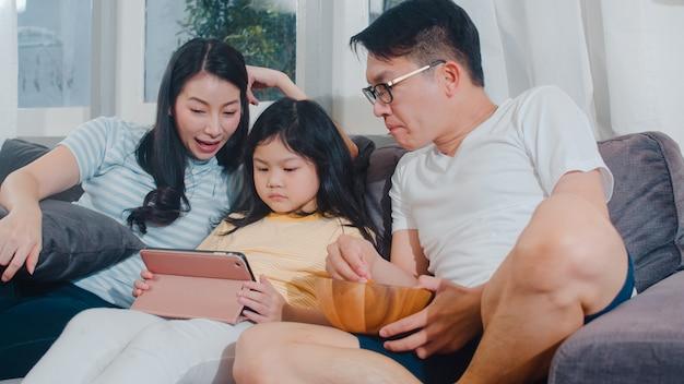 Junge asiatische familie und tochter glücklich, tablette zu hause verwendend. japanische mutter, vater entspannen sich mit dem aufpassenden film des kleinen mädchens, der auf sofa im wohnzimmer liegt. lustiges elternteil und reizendes kind haben spaß. Kostenlose Fotos