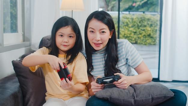 Junge asiatische familie und tochter spielen spiele zu hause. koreanische mutter mit dem kleinen mädchen, das zusammen lustigen glücklichen moment des steuerknüppels auf sofa im wohnzimmer am haus verwendet. lustige mutter und schönes kind haben spaß Kostenlose Fotos