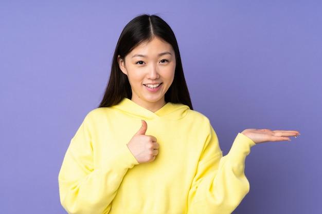 Junge asiatische frau auf lila wand, die leerzeichen hält Premium Fotos