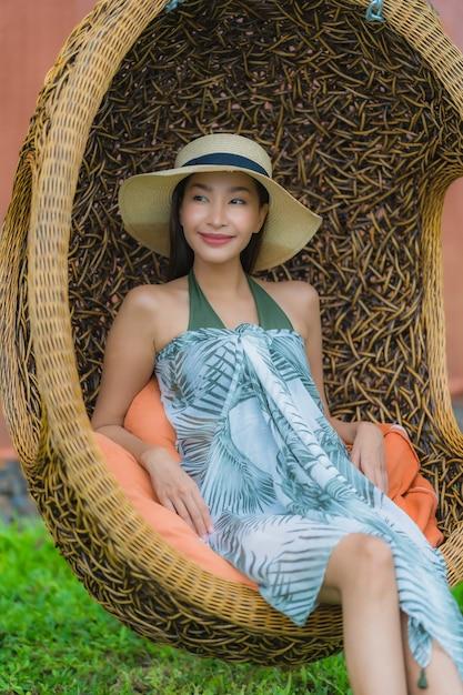 Junge asiatische frau des porträts, die auf schwingenstuhl im garten sitzt Kostenlose Fotos