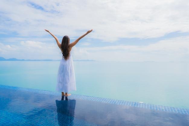 Junge asiatische frau des porträts entspannen sich das lächeln, das um swimmingpool im hotel und im erholungsort glücklich ist Kostenlose Fotos