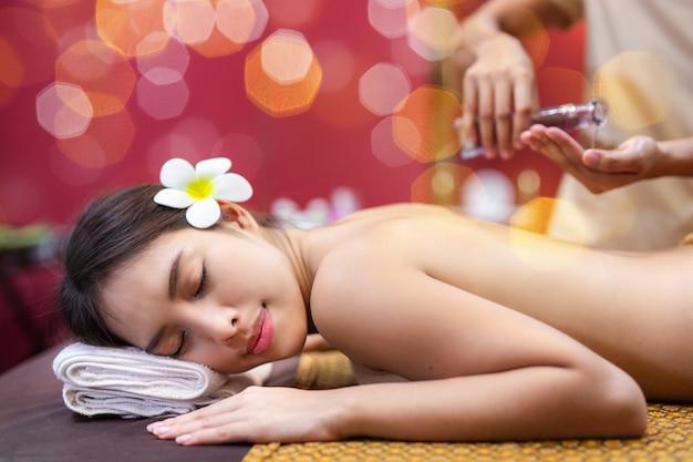 Junge asiatische frau, die auf bett in der badekurortmassage liegt. Premium Fotos