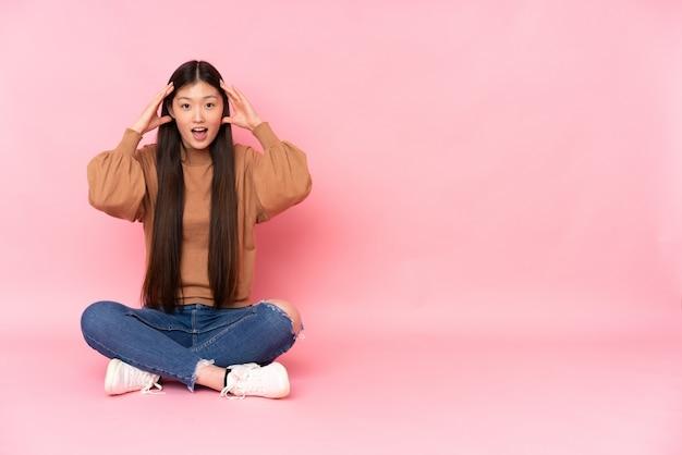 Junge asiatische frau, die auf dem boden auf rosa wand mit überraschungsausdruck sitzt Premium Fotos