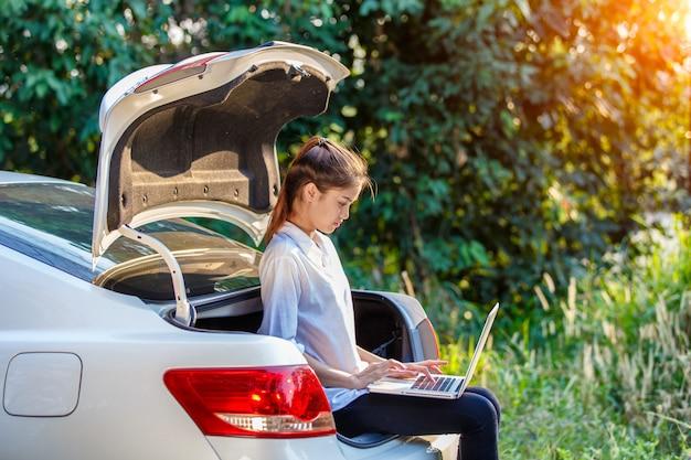 Junge asiatische frau, die auf hatchbackauto mit notizbuch sitzt Premium Fotos