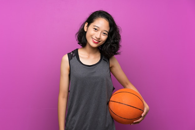 Junge asiatische frau, die basketball über getrennter purpurroter wand spielt Premium Fotos