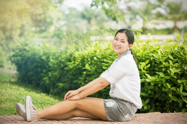 Junge asiatische frau, die draußen sich entspannt und glücklich lächelt Premium Fotos