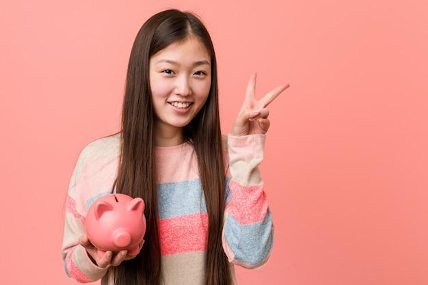 Junge asiatische frau, die ein sparschwein zeigt siegeszeichen und breit lächelt hält. Premium Fotos