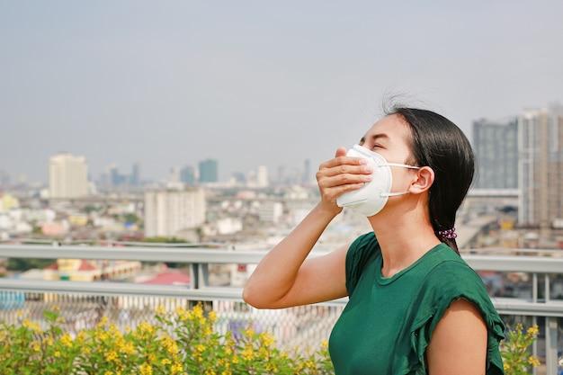 Junge asiatische frau, die eine schutzmaske trägt Premium Fotos