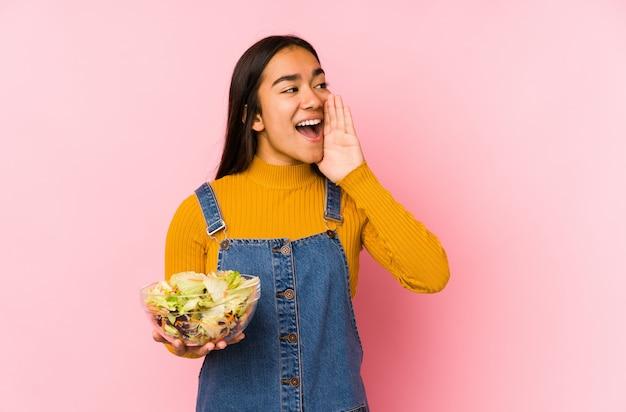 Junge asiatische frau, die einen salat lokalisierte, der schreit und handfläche nahe geöffnetem mund hält. Premium Fotos