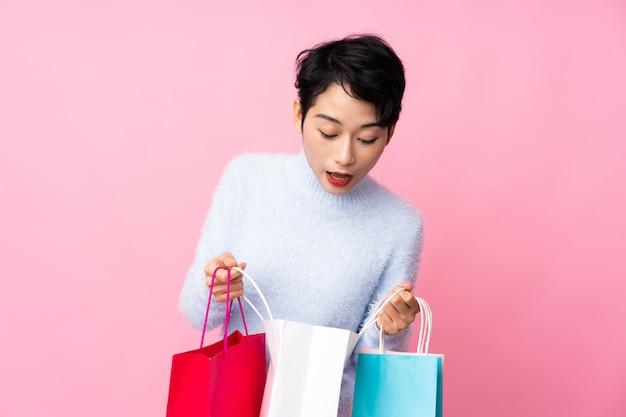Junge asiatische frau, die einkaufstaschen hält und darin schaut Premium Fotos