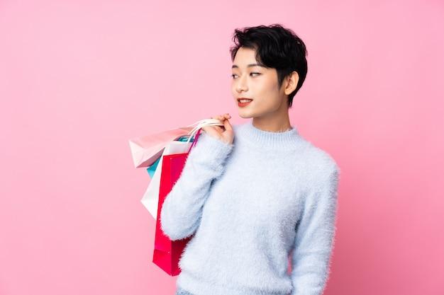 Junge asiatische frau, die einkaufstaschen hält und zurückblickt Premium Fotos