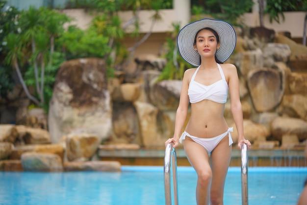 Junge asiatische frau, die im schwimmbad entspannt Premium Fotos