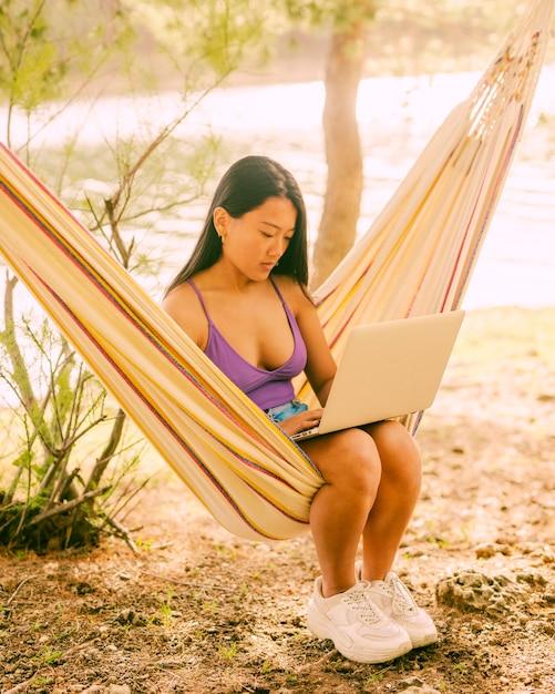 Junge asiatische frau, die in der hängematte nahe fluss sitzt und auf laptop freiberuflich arbeitet Kostenlose Fotos