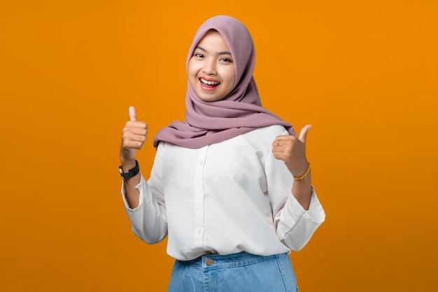 Junge asiatische frau, die lächelt und daumen auf gelb macht Premium Fotos