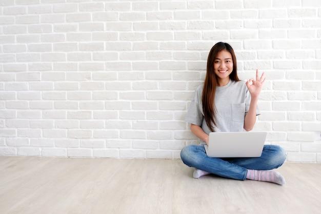 Junge asiatische frau, die okayhandzeichen zeigt und beim arbeiten mit laptop-computer im reinraum lächelt Premium Fotos