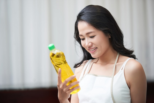Junge asiatische frau, die reinigende flasche erforscht Kostenlose Fotos