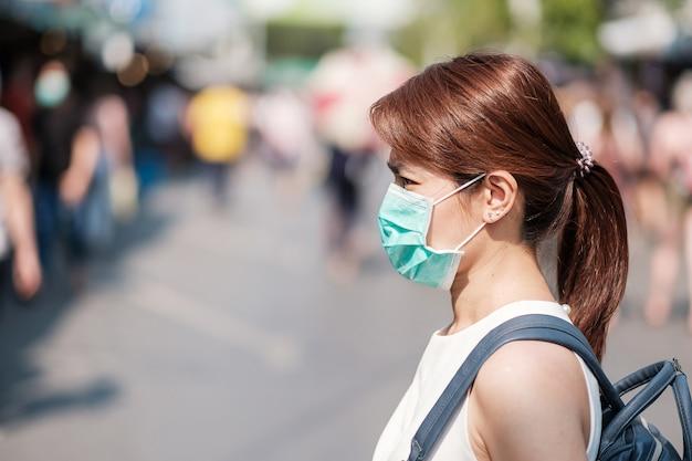 Junge asiatische frau, die schutzmaske gegen neuartiges coronavirus (2019-ncov) oder wuhan coronavirus am chatuchak-wochenendmarkt trägt, wahrzeichen und beliebt für touristenattraktionen Premium Fotos