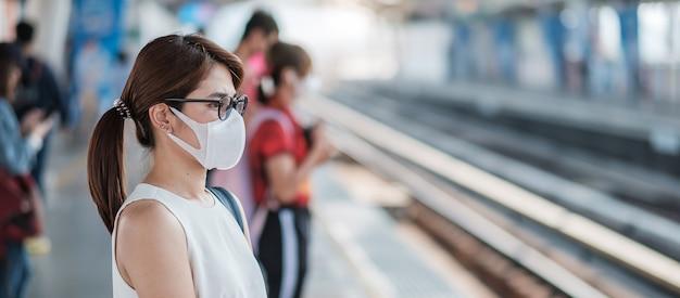 Junge asiatische frau, die schutzmaske gegen neuartiges coronavirus (2019-ncov) oder wuhan coronavirus am öffentlichen bahnhof trägt, ist ein ansteckendes virus, das atemwegsinfektion verursacht Premium Fotos