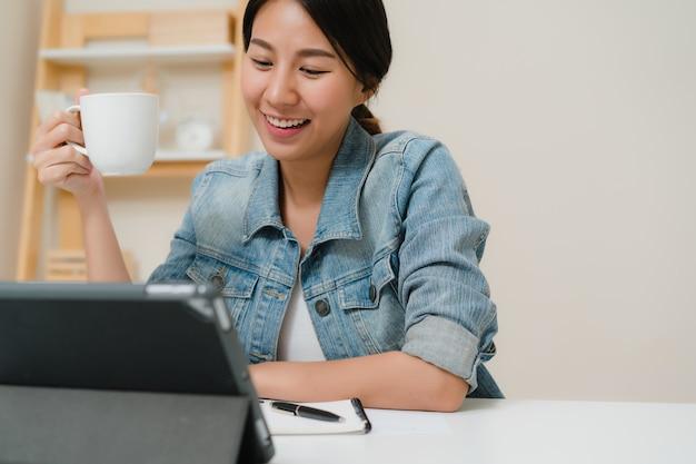 Junge asiatische frau, die unter verwendung der tablette social media überprüfend und trinkenden kaffee arbeitet, während sie sich zu hause auf schreibtisch im wohnzimmer entspannen. Kostenlose Fotos
