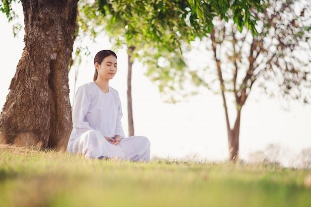 Junge asiatische frau entspannt sich tragende weiße kleidermeditation an den grünen rasenflächen Premium Fotos