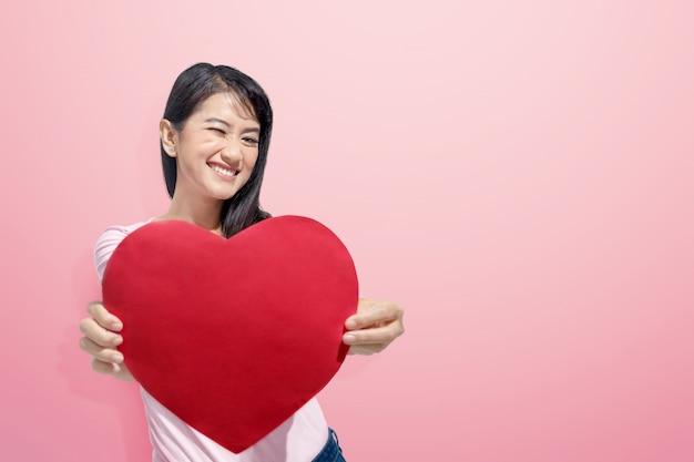 Junge asiatische frau mit rotem herzen auf ihren händen Premium Fotos