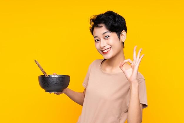 Junge asiatische frau über isolierter gelber wand, die ok zeichen mit den fingern zeigt, während eine schüssel nudeln mit stäbchen hält Premium Fotos